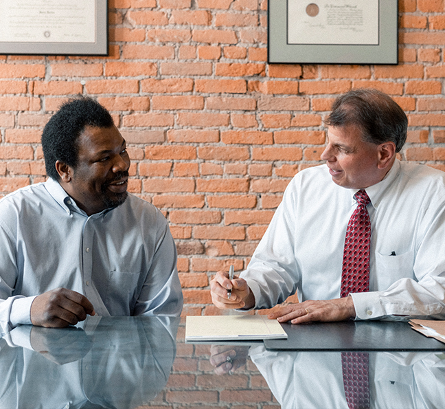 landlord lawyer near syracuse ny image of attorney gary valerino and client talking